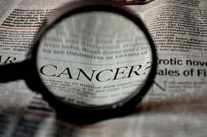 Is Alpha Lipoic Acid a Nootropic - The Word Cancer Under Magnifying Glass in Newspaper Headline