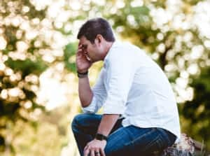 What is Ashwagandha for - Stressed Man Sitting on Tree Trunk in Park